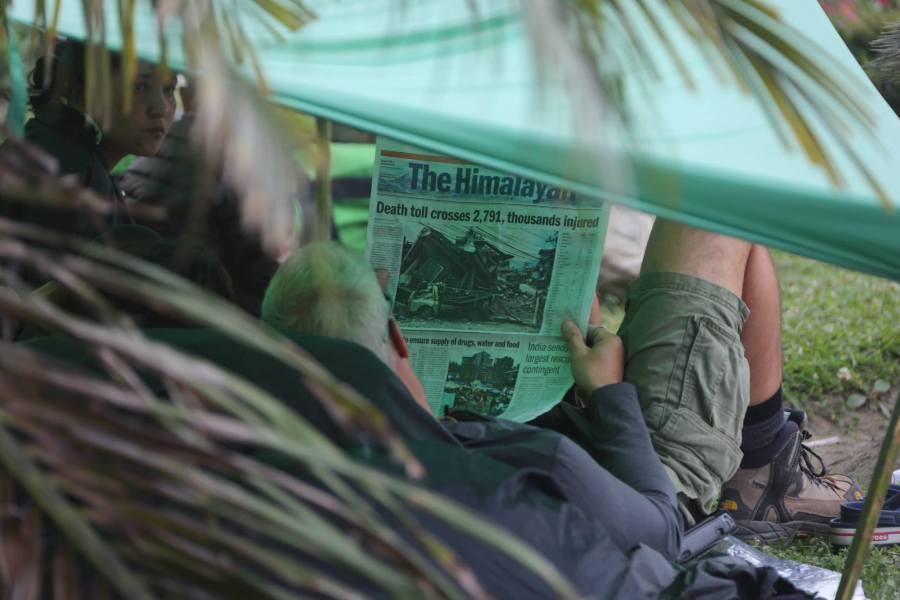 A flyer whose flight is probably delayed under a tent reading The Himalayan Times. 27 April 2015.