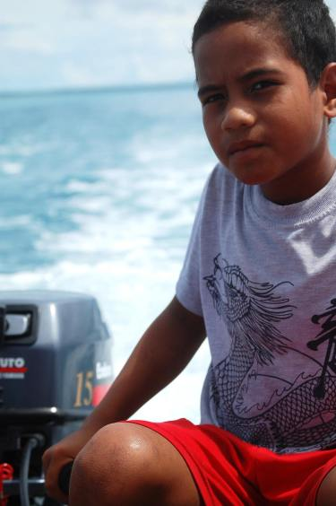 """You can drive a boat before you can drive a motorbike/car"" says the boy's father. 11 years old Tapugao steering the boat on a family trip to motu."